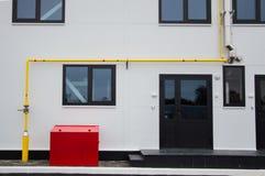 Erdgasrohr Yelow, Edelstahlabgasrohr und Kasten des roten Feuers installiert vor dem modernen Gebäude Stockfotos