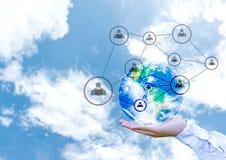 Erdkugel mit Vernetzungssystem in der männlichen Palme auf abstraktem Hintergrund des blauen Himmels Lizenzfreies Stockfoto