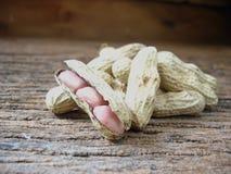 Erdnüsse auf altem hölzernem Hintergrund Stockbilder