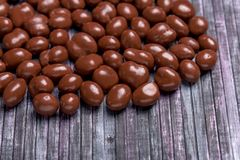 Erdnüsse in der Schokolade Süße Erdnuss im Hintergrund Hölzerner Hintergrund Süße Erdnüsse in der Schokolade für Tee und Kaffee Lizenzfreie Stockbilder