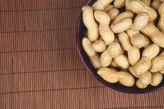 Erdnüsse in einer keramischen Schüssel auf einem hölzernen Hintergrund Stockfotos