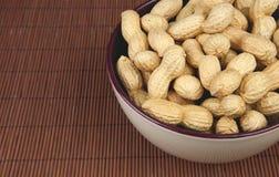 Erdnüsse in einer keramischen Schüssel auf einem hölzernen Hintergrund Lizenzfreie Stockfotos