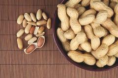 Erdnüsse in einer keramischen Schüssel auf einem hölzernen Hintergrund Lizenzfreies Stockbild