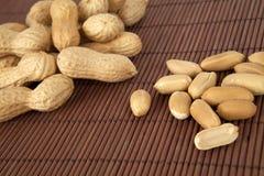 Erdnüsse in einer keramischen Schüssel auf einem hölzernen Hintergrund stockfotografie