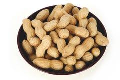 Erdnüsse in einer keramischen Schüssel auf einem weißen Hintergrund lizenzfreies stockbild