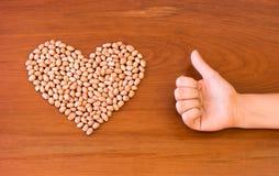 Erdnüsse formten in ein Herz nahe bei Daumen oben auf einer Holzoberfläche Lizenzfreies Stockbild