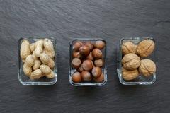 Erdnüsse, Haselnüsse und Walnüsse mit den Nussschalen gelegt in Glasplatten auf schwarze Steinhintergrund-Oberfläche stockfotografie