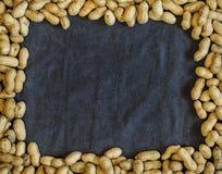 Erdnüsse im Oberteil auf dunklem Textilhintergrund Stockbilder