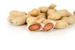Erdnüsse mit Oberteil auf einem weißen Hintergrund Stockbilder
