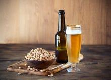 Erdnüsse und Bier Stockfotografie