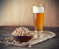 Erdnüsse und ein Bier Stockbilder