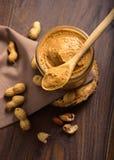 Erdnüsse und Erdnussbutter auf hölzernem Hintergrund Stockfoto