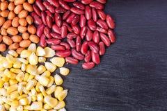 Erdnüsse und rote Bohnen und Mais auf schwarzem hölzernem Brett Stockfoto