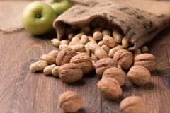 Erdnüsse, Walnüsse, grüne Äpfel auf einem hölzernen Hintergrund Stockfoto