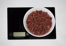 Erdnuss auf einer digitalen weißen Küchenskala Lizenzfreie Stockfotos