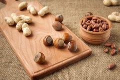 Erdnuss, Haselnüsse in den hölzernen Schüsseln auf hölzernem und Leinwand, Sackhintergrund Lizenzfreies Stockfoto