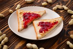 Erdnussbutter und Geleesandwich auf hölzernem Hintergrund lizenzfreies stockfoto
