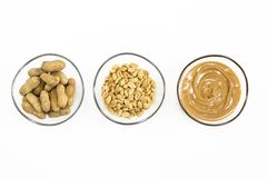 Erdnussbutter und Nüsse in drei Schüsseln lokalisiert auf Weiß lizenzfreie stockbilder