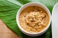 Erdnussbutter und zerquetschte Erdnüsse in einer weißen Schüssel Stockfoto