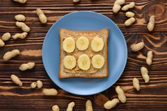 Erdnussbuttertoast mit Bananenscheiben auf hölzernem Hintergrund lizenzfreie stockfotos