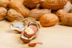 Erdnusskerne mit gebrochenen shelles auf hölzernem Stockfotografie