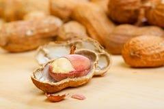 Erdnusskerne mit gebrochenen shelles auf hölzernem Lizenzfreies Stockbild