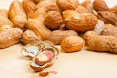 Erdnusskerne mit gebrochenen shelles auf hölzernem Stockfoto
