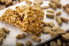 Erdnusssprödes oder Erdnuss chikki und gebratene Erdnüsse Lizenzfreie Stockfotografie