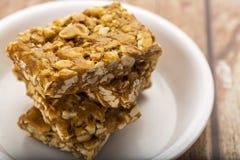 Erdnusssprödes oder Erdnuss chikki und gebratene Erdnüsse Stockfotos