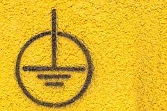 Erdung des Zeichens auf der Gelb vergipsten Wand Stockbilder