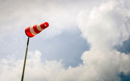 Erect red and white windsock on a pole. Erect windsock with red and white stripes on a tall post and against a menacing and darkening sky. Bad weather is coming royalty free stock image