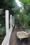 Erecting Fencing in vegetation. Erecting Fencing in vegitation with cement wheelbarrow Royalty Free Stock Photos