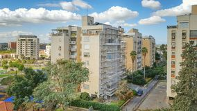 The erection of balconies of the 8-story building. Ness Ziona, Israel-March 11, 2018: Mounted scaffolding around the 8-floor living tower is for painting the royalty free stock photography