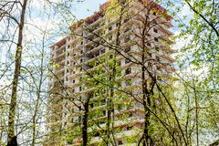 The erection of a high-rise multi-apartment building in the forest. Urbanization stock image