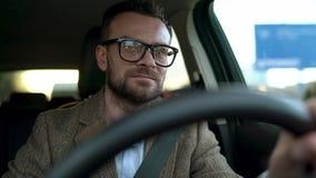 Erfüllter bärtiger Mann im Glasautofahren hinunter die Straße im sonnigen Wetter stock video