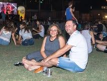 Erfüllte Besucher sitzen auf dem Gras und dem Rest am traditionellen jährlichen Bierfestival in der Stadt von Haifa in Israel Lizenzfreies Stockbild