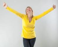 Erfüllte blonde Frau 20s, die ihre Arme für Wohl ausstreckt Lizenzfreie Stockbilder