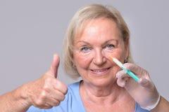 Erfüllte Frau mit Einspritzung auf Gesicht Lizenzfreies Stockbild