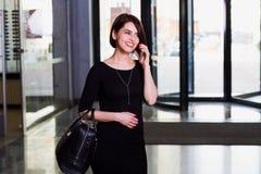 Erfüllte Geschäftsdame im Einkaufszentrum, sprechend am Telefon Lizenzfreie Stockfotografie