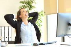 Erfüllte Geschäftsfrau, die im Büro sich entspannt stockfotos