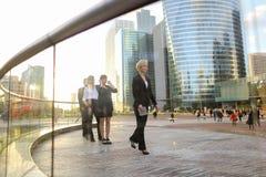 Erfüllte Geschäftsfrau, die mit Dokumentenfall und -partnern geht Lizenzfreies Stockbild