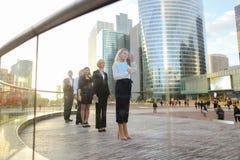 Erfüllte Geschäftsfrau, die mit Dokumentenfall und -partnern geht Stockfotografie
