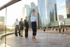 Erfüllte Geschäftsfrau, die mit Dokumentenfall und -partnern geht Lizenzfreie Stockfotos