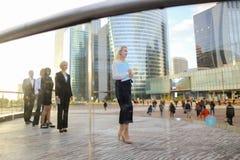 Erfüllte Geschäftsfrau, die mit Dokumentenfall und -partnern geht Stockbilder