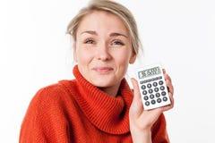 Erfüllte junge blonde Studentin, die ihren Taschenrechner zeigend genießt Lizenzfreie Stockfotos