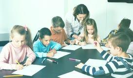 Erfüllte kleine Kinder mit Lehrerzeichnung im Klassenzimmer Stockbilder