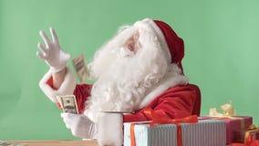 Erfüllte werfende Rechnungen Santa Clauss aus einem Bündelgeld auf Tabelle heraus, Geldkonzept, chromakey im Hintergrund stock video