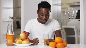 Erfüllter Afroamerikanermann, der frischen Saft trinkt stock video footage