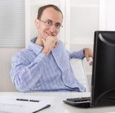 Erfüllter Geschäftsmann, der in seinem Büro mit Computer sitzt Stockfoto