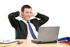 Erfüllter Geschäftsmann, der seinen Laptop betrachtet Lizenzfreies Stockbild